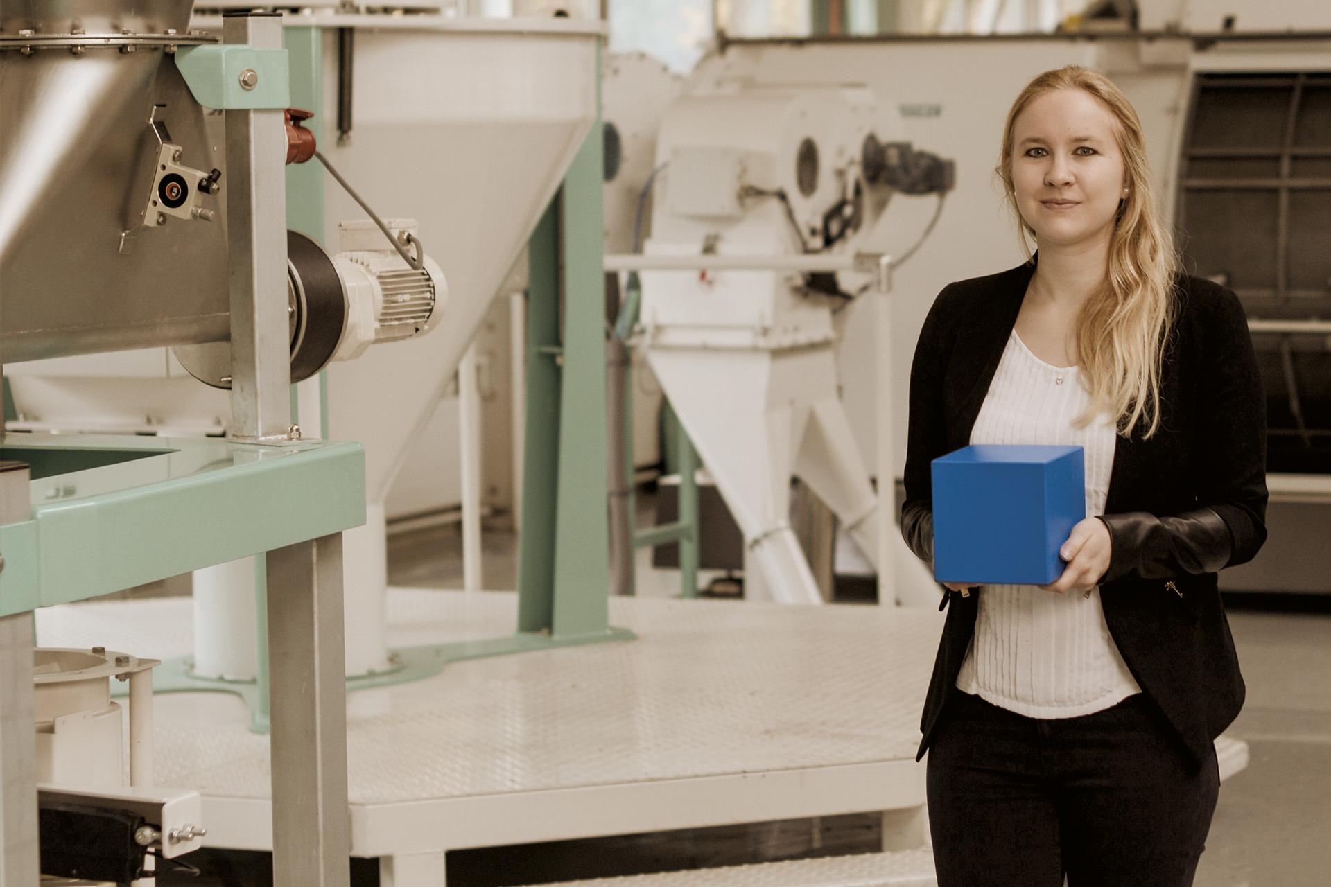 Eine Studentin steht in einem Betrieb mit Maschinen und hält einen blauen Würfel in den Händen.