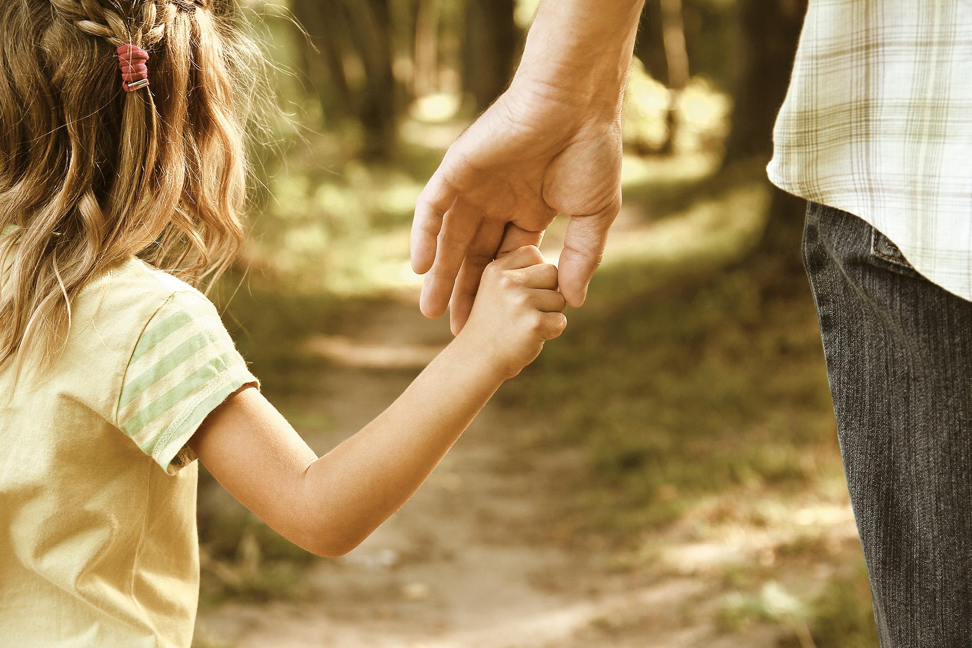 Ein Mädchen hält eine erwachsene Person an der Hand.