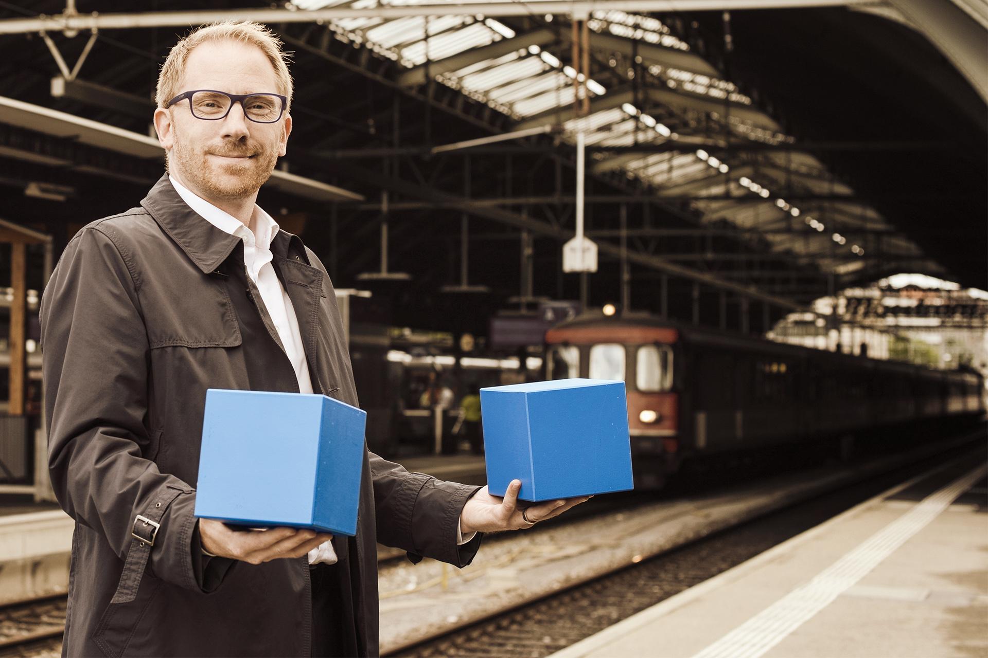 Ein Student steht auf dem Perron eines Bahnhofs und hält zwei blaue Würfel in den Händen.