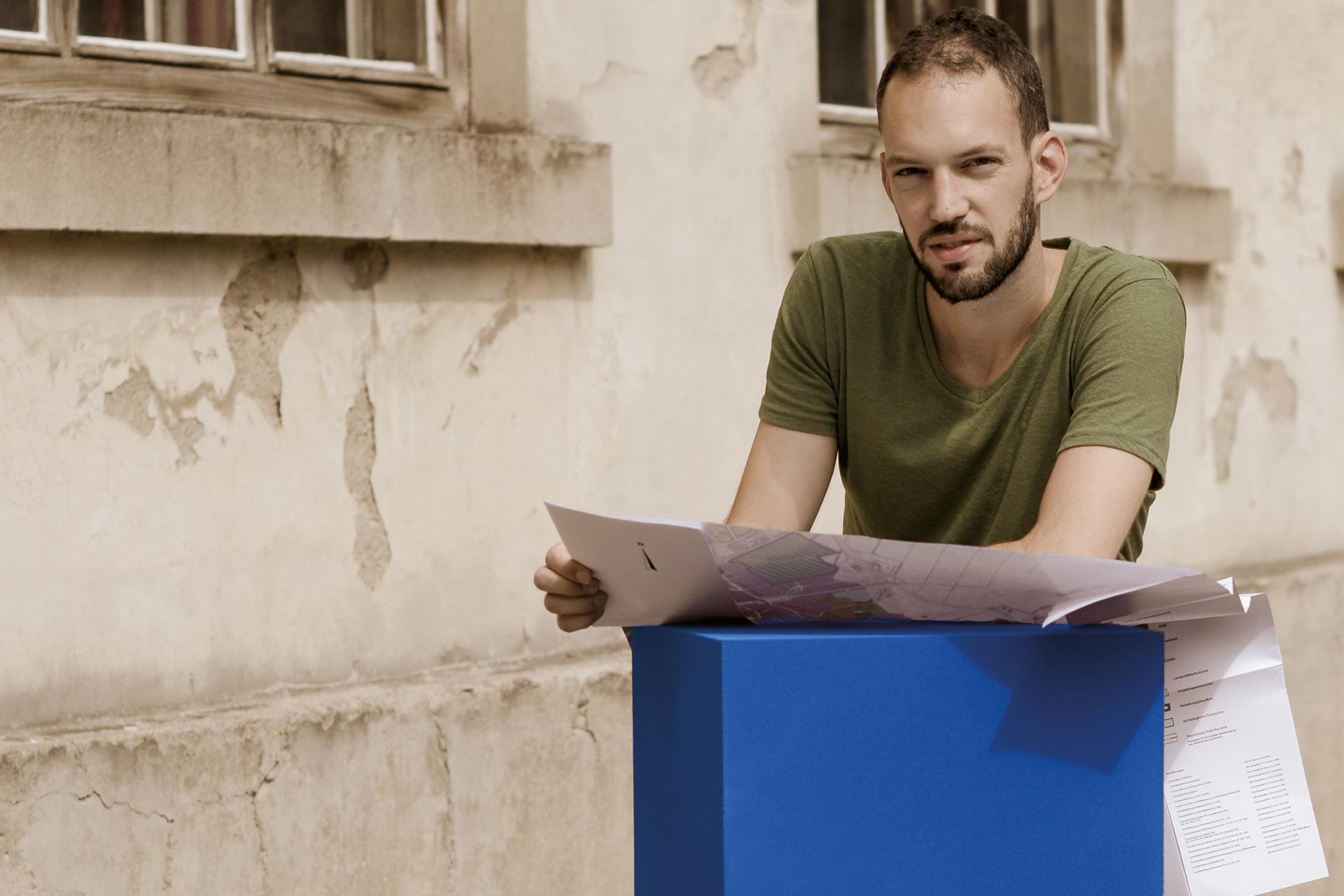 Ein Student der FHS St.Gallen studiert Baupläne, die auf einem blauen Quader liegen.