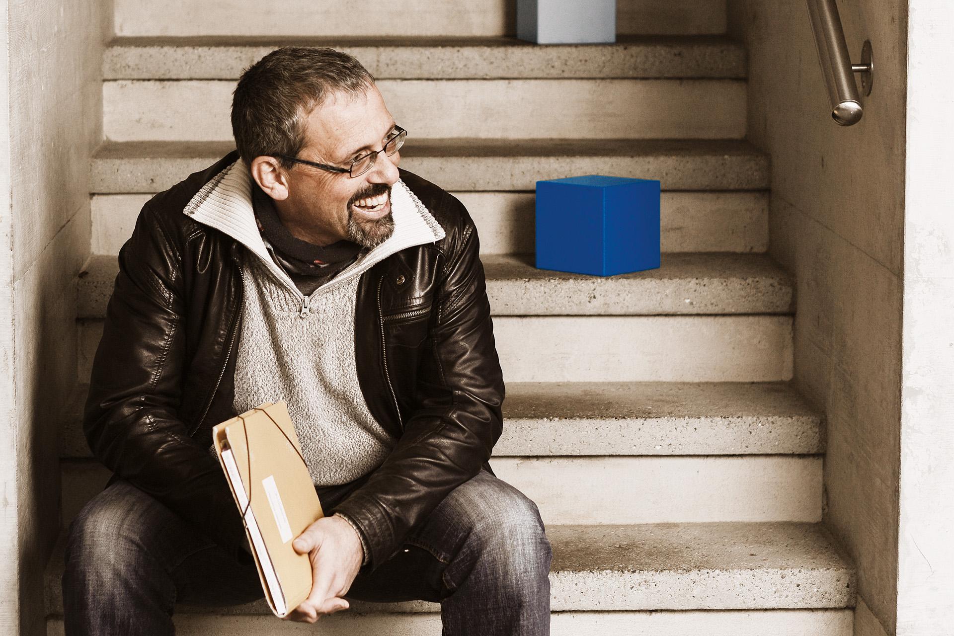 Ein Student der FHS St.Gallen sitzt auf einer Treppe. Er hält eine Mappe in den Händen.