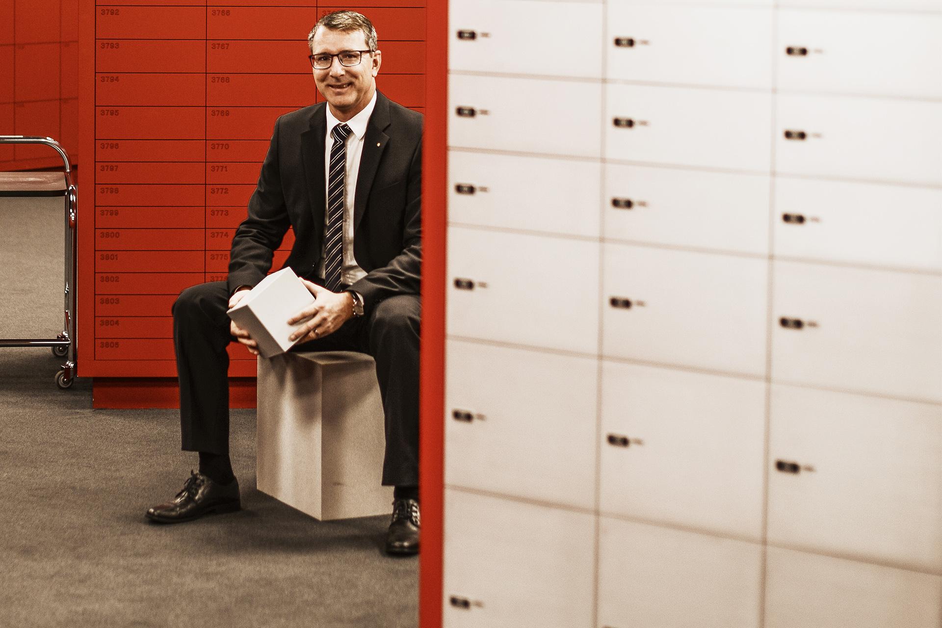 Ein Mann sitzt auf einem Kubus im Schrankfachraum einer Bank.