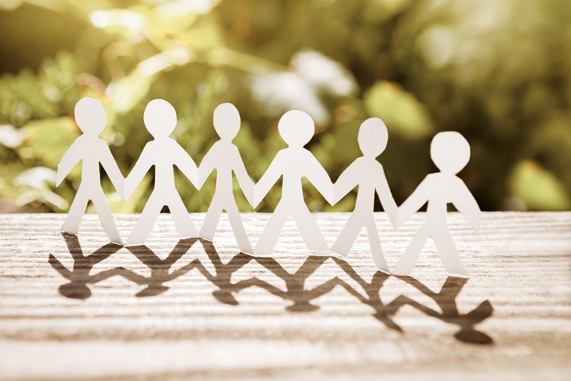 Ein Scherenschnitt symbolisiert Kinder, die sich an den Händen halten.