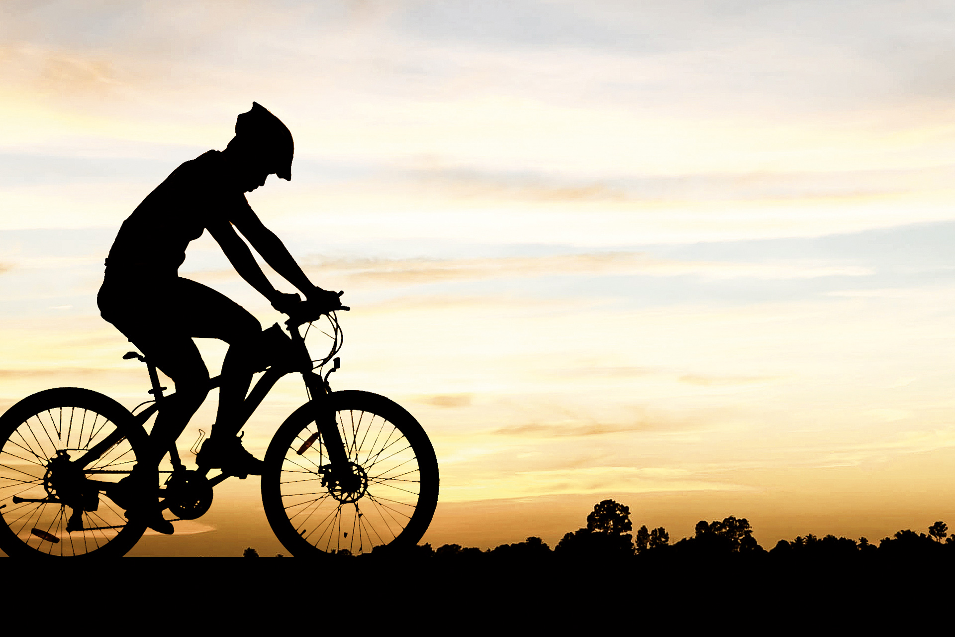 Das Bild zeigt die Silhouette eines Fahrradfahrers vor einem Sonnenuntergang.